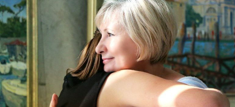 an older woman hugging a daughter