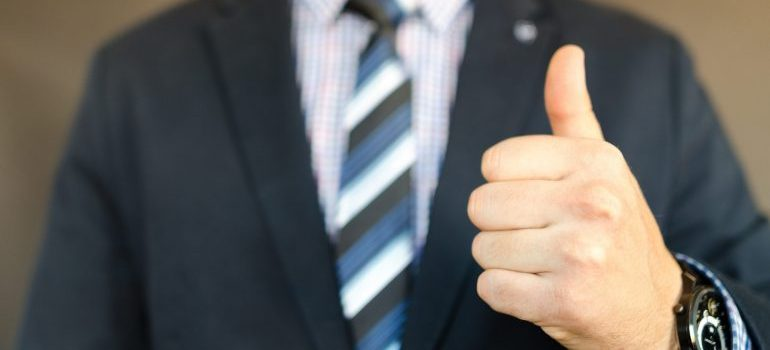 Person in black suit with a thumb up