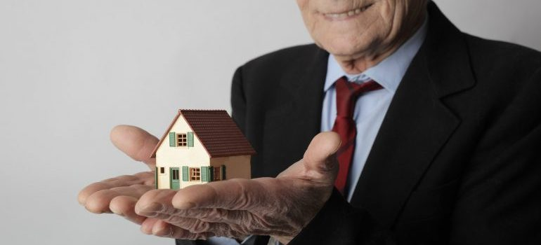 Man holding a miniature house