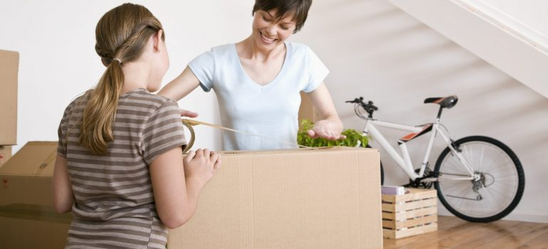 Woman and daughter taping moving boxes