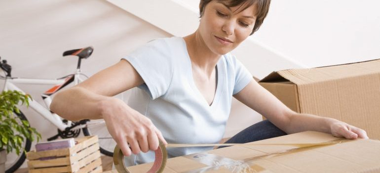 Woman taping moving boxes - residential movers Pottstown PA
