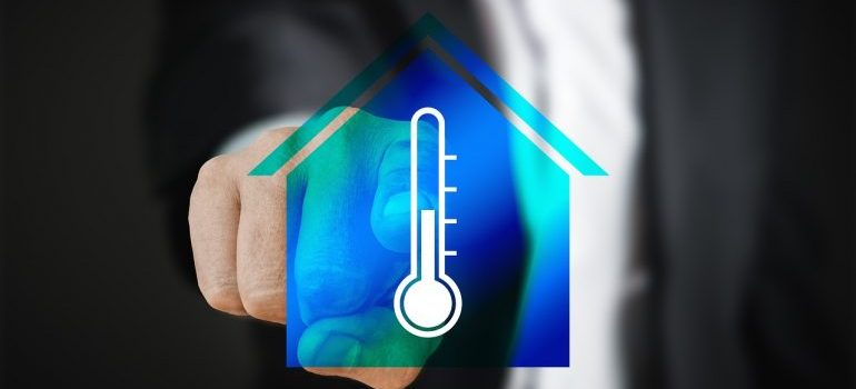 Person in black suit pointing at a thermometer