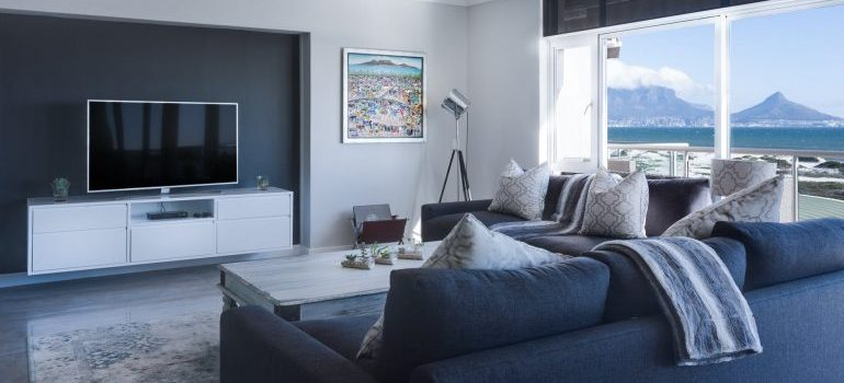 room-by-room packing guideliness are useful. A living room with a TV and a sofa in grey color