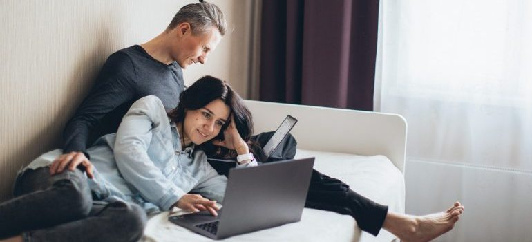 Couple reading on the internet how to make new firends after relocating