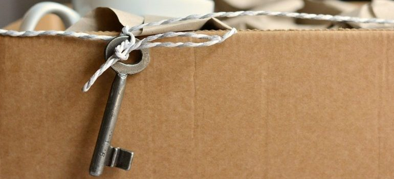 A moving box with a key sticking out of the top