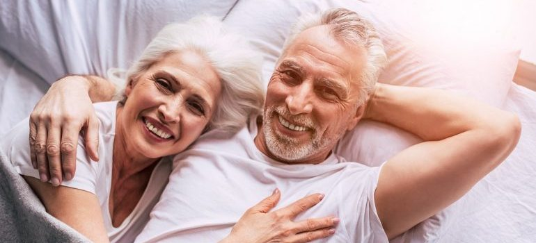 Old couple lying in bed and smiling