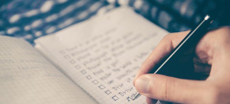a hand writing down a checklist
