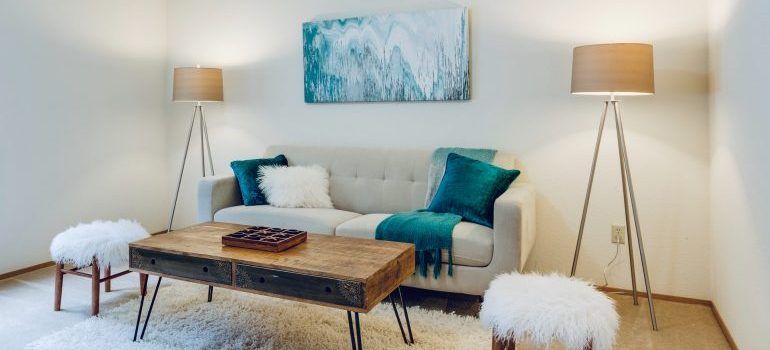 A wooden table in front of a grey sofa with blue pillows as an example of a way you could stage your Philly apartment for sale.