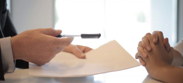 Picture of two people signing a document.