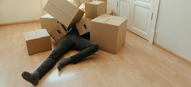 A man lying on the floor covered by cardboard boxes for storage during a move to Norristown.