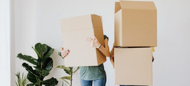 A couple holding moving boxes.