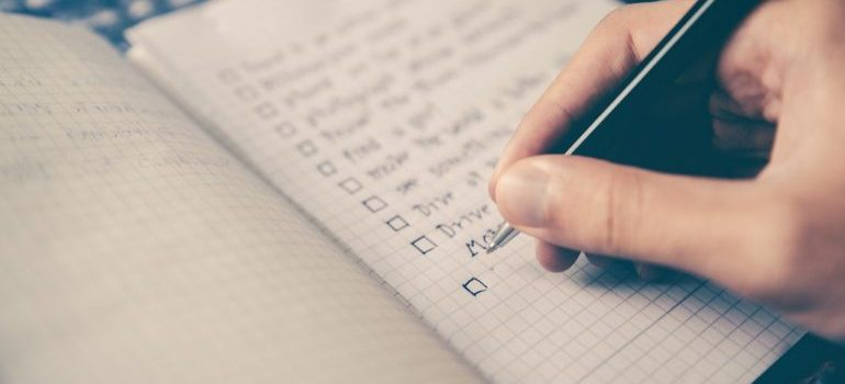 A person writing their moving checklist.