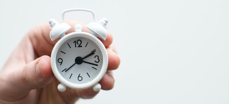 A person holding a small clock.
