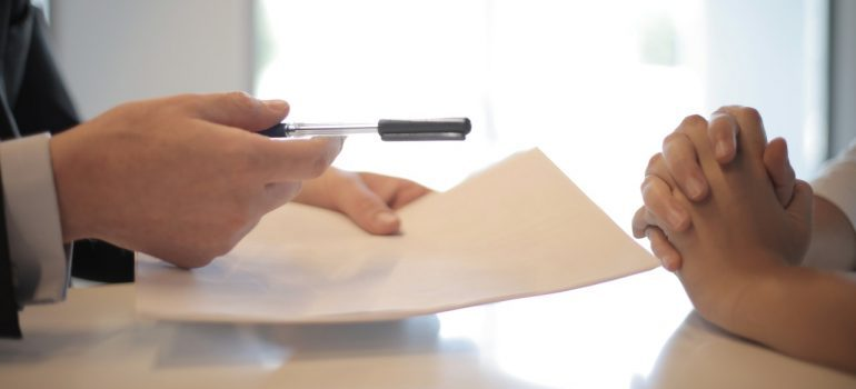 A man giving a contract to another person.