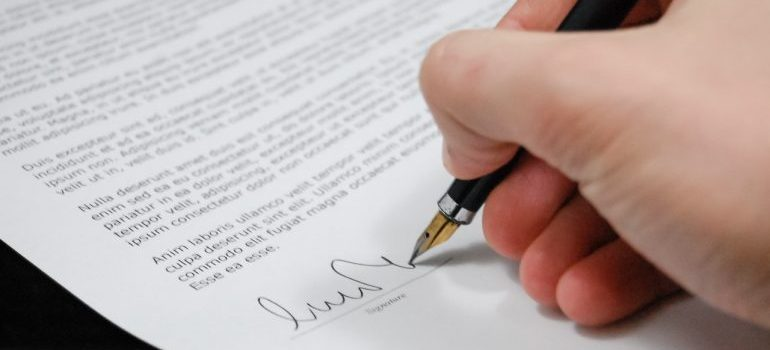 Picture of a man signing a contract.