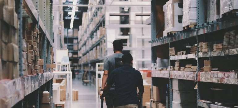 Two men in a warehouse to inspect it when it is time to rent a warehouse.
