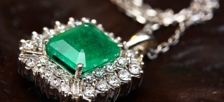 A silver pendant with a green gemstone.