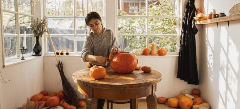 A girl carving a pumpkin.