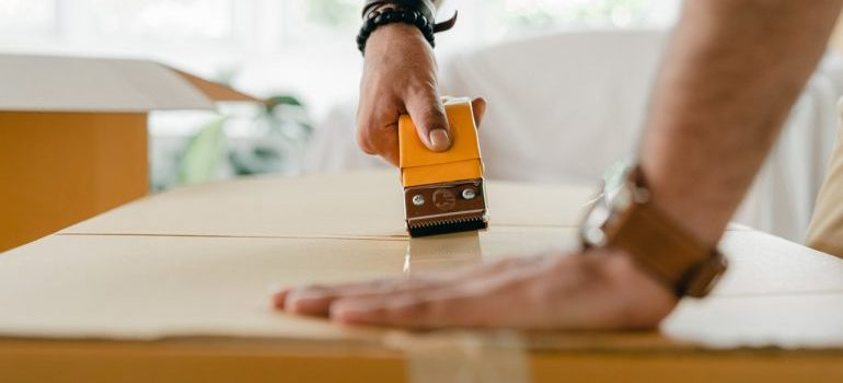 A person sealing a carboard box.