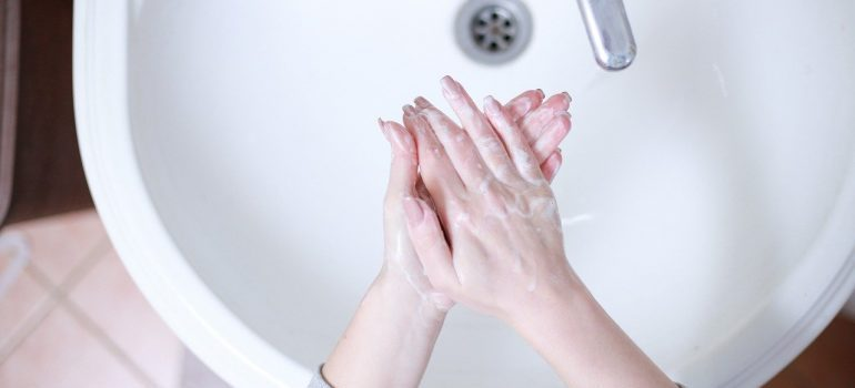 A person washing their hands after cleaning an apartment after movers.