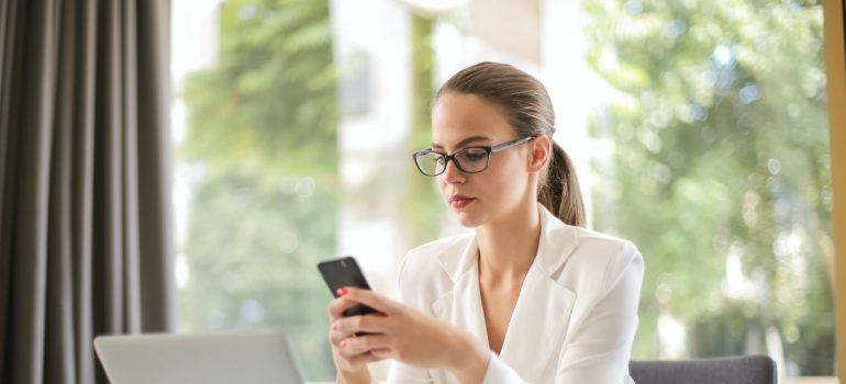 A girl using her phone in order to find a job in Glenside after the relocation.