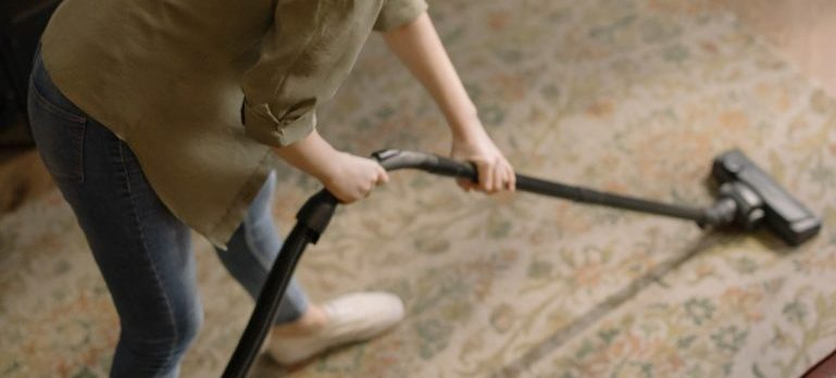 A person vacuuming a room.