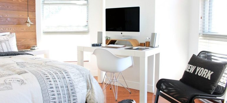 An unpacked bedroom with a computer and a chair showing the importance of unpacking in the right order.