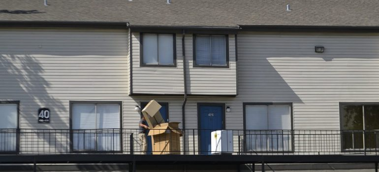 A man carrying boxes into a home.