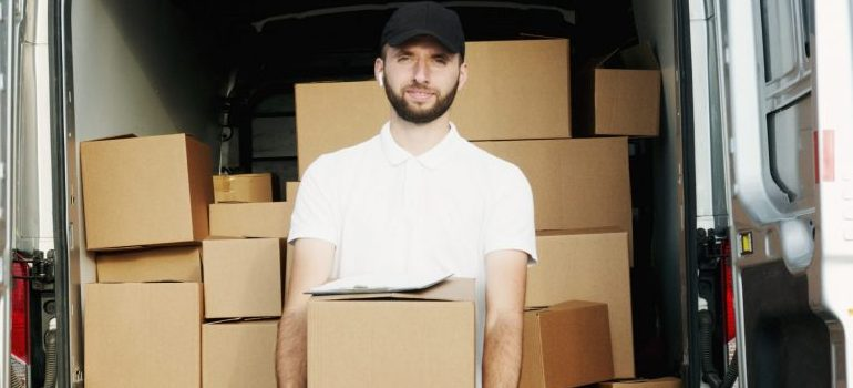 a man in a white shirt and a black hat holding a moving box