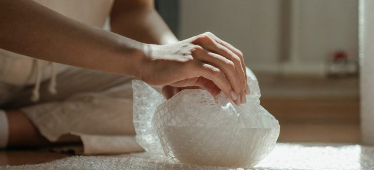 A person packing for the move using bubble wrap