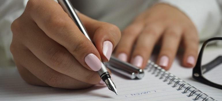 A person writing something in a notebook in order to prepare for a local relocation.