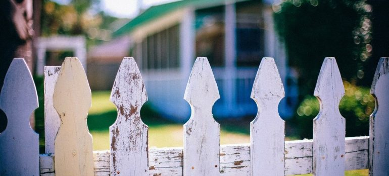 a wooden fence separating the neighbours front yard