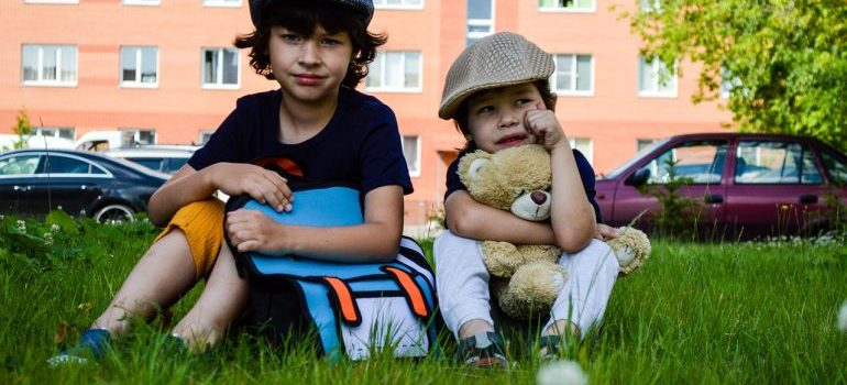 kids with a backpack sitting on the grass