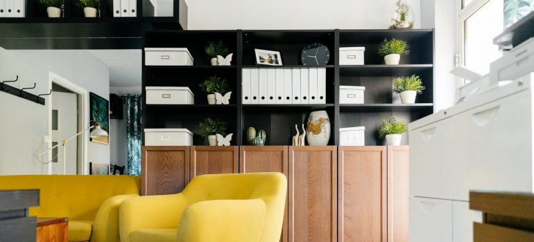 a living room with yellow furniture and full shelves on the wall that show how to make storage space in your apartment