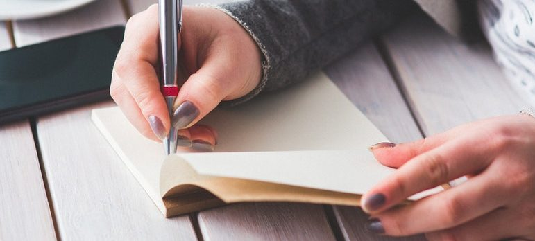 A woman writing on a piece of paper