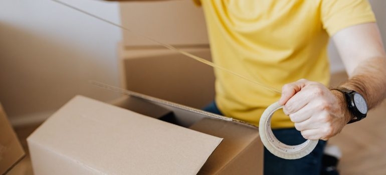 a man putting tape over the cardboard box after he finished packing