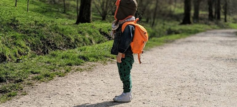 kid standing with a packed backpack