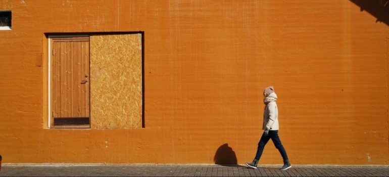 a man in a white jacket walking past an orange wall in Lansdale after the move