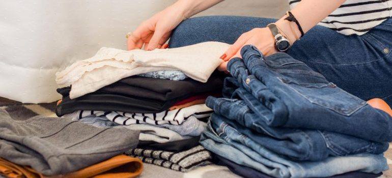 A woman folding clothes and giving an example of how you should treat the items you do not have enough room for such as clothing