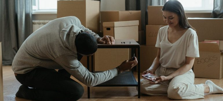 a couple disassembling a coffee table after choosing items for storage