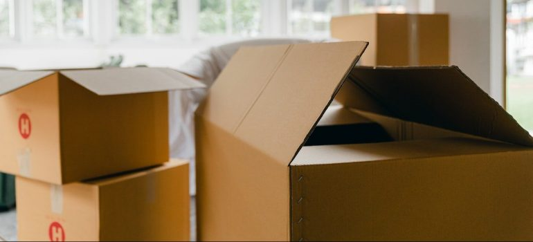 a stack of cardboard boxes inside a living room as a way to avoid cluttering your storage