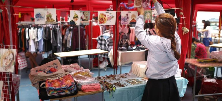 a girl hanging a picture atop of her stand where she sells various items
