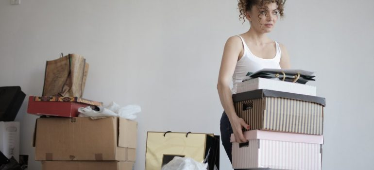 a woman carrying boxes from her living room