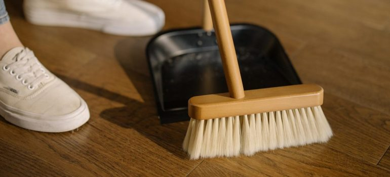 a picture of a woman cleaning the floor with a dustpan and a broom as you should when preparing your storage for spring