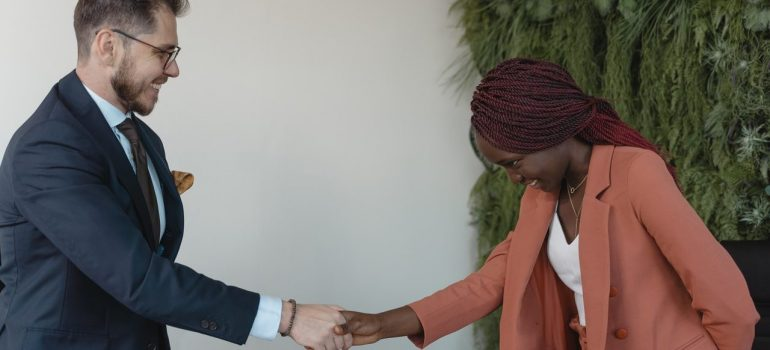 a woman shaking a mans hand after being accepted for a job