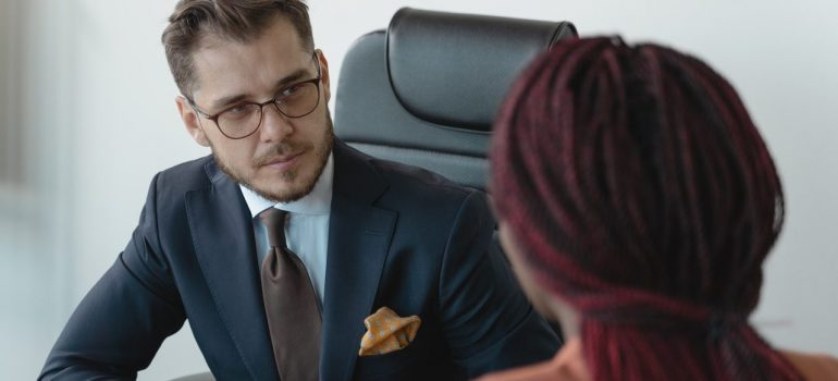 a man in a suit having a job interview with a woman in a red suit as a way to find a job in Downingtown