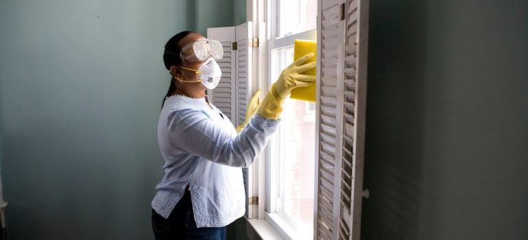 A woman in cleaning equipment cleaning a window