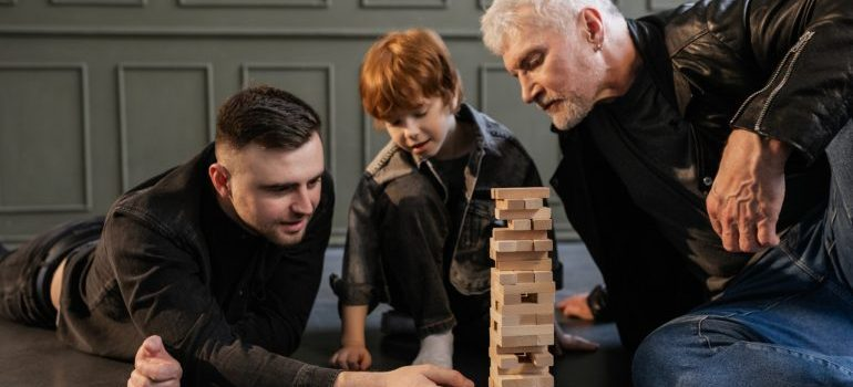 Father and a granfather playing jenga with the child.