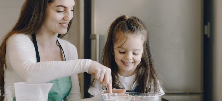 woman and a little girl in the kitchen, making cookies