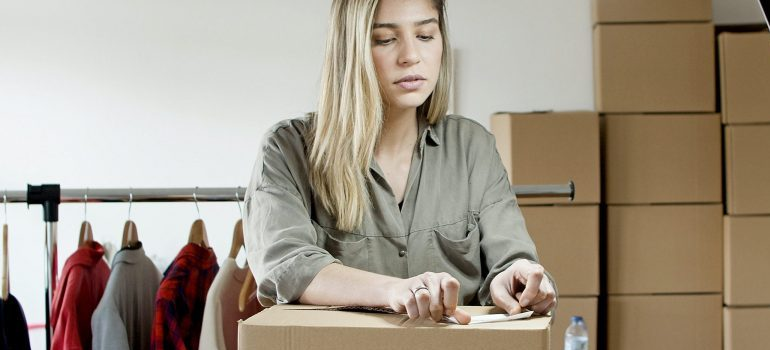 woman packing for the move, closing a moving box